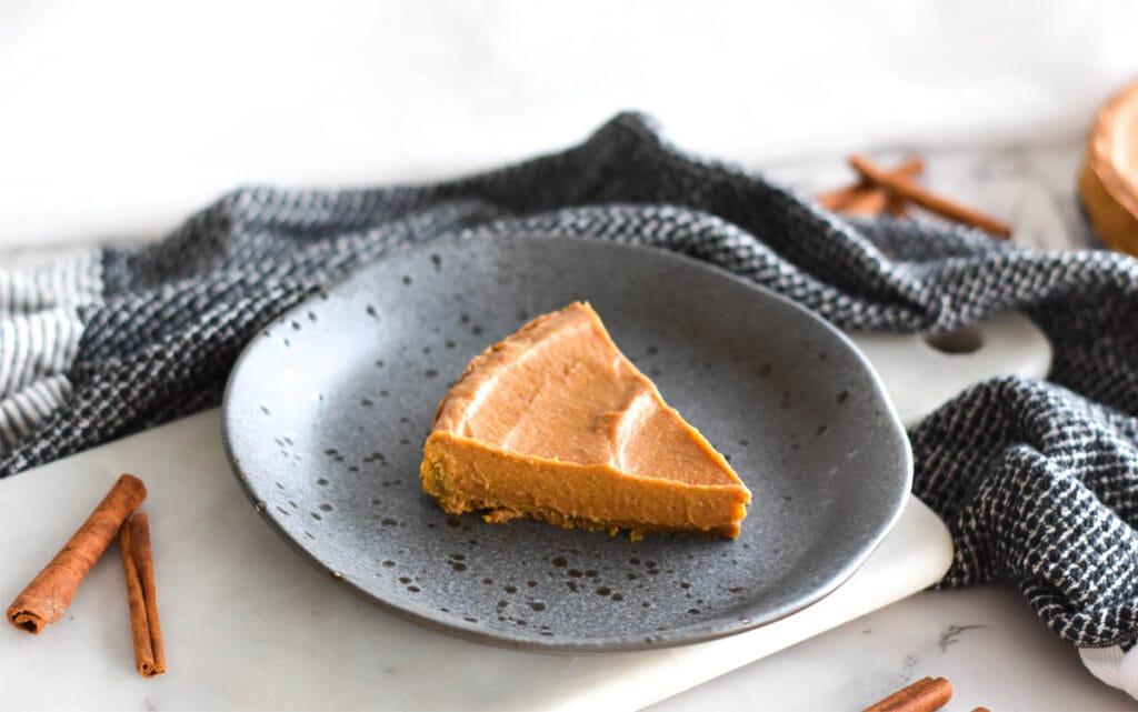Slice of Paleo AIP pumpkin pie on a stoneware plate next to cinnamon sticks.