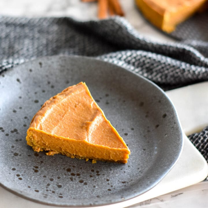 Slice of pumpkin pie on a black stoneware plate.