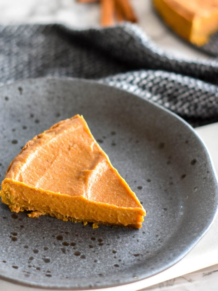 Slice of pumpkin pie on a black stoneware plate.