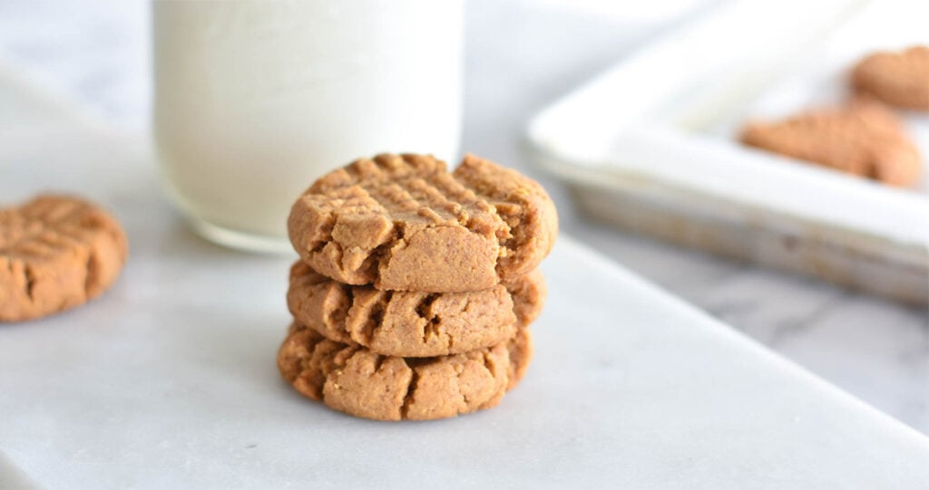 Stack of three keto peanut butter cookies next to tray of cookies and a glass of milk.
