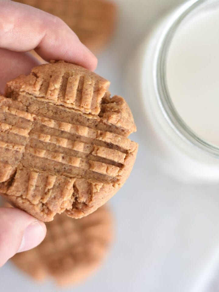 Hand holding keto peanut butter cookie over glass of milk.