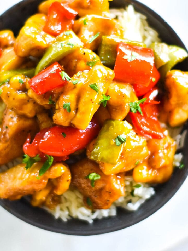 Close up shot of a dark bowl with brightly colored chicken and bell peppers on a bed of rice.