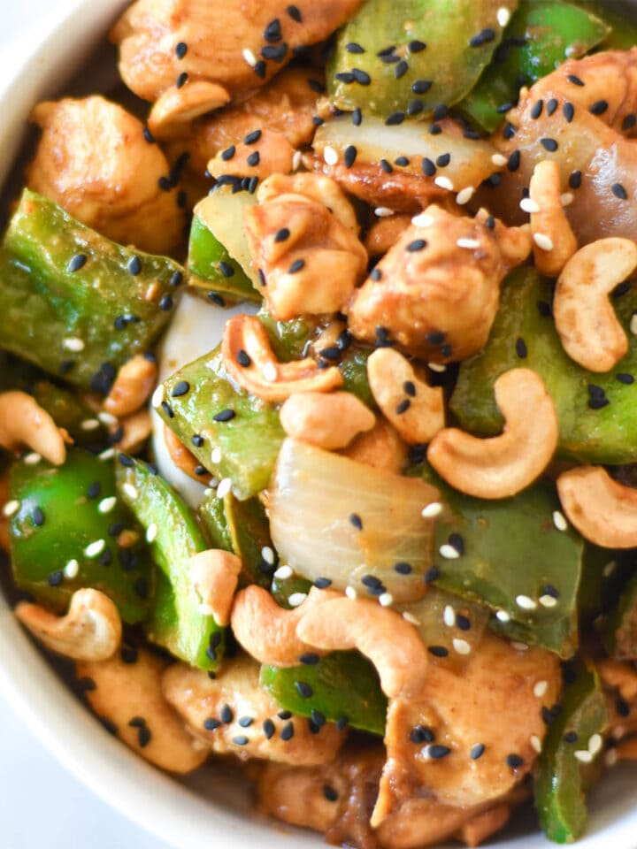 Bowl of chicken with green bell peppers, onions, cashews and black sesame seeds.