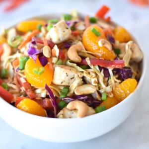Bowl of Paleo Asian Chicken Salad with brightly colored mandarin oranges, bell peppers, green onions, cabbage and cashews.