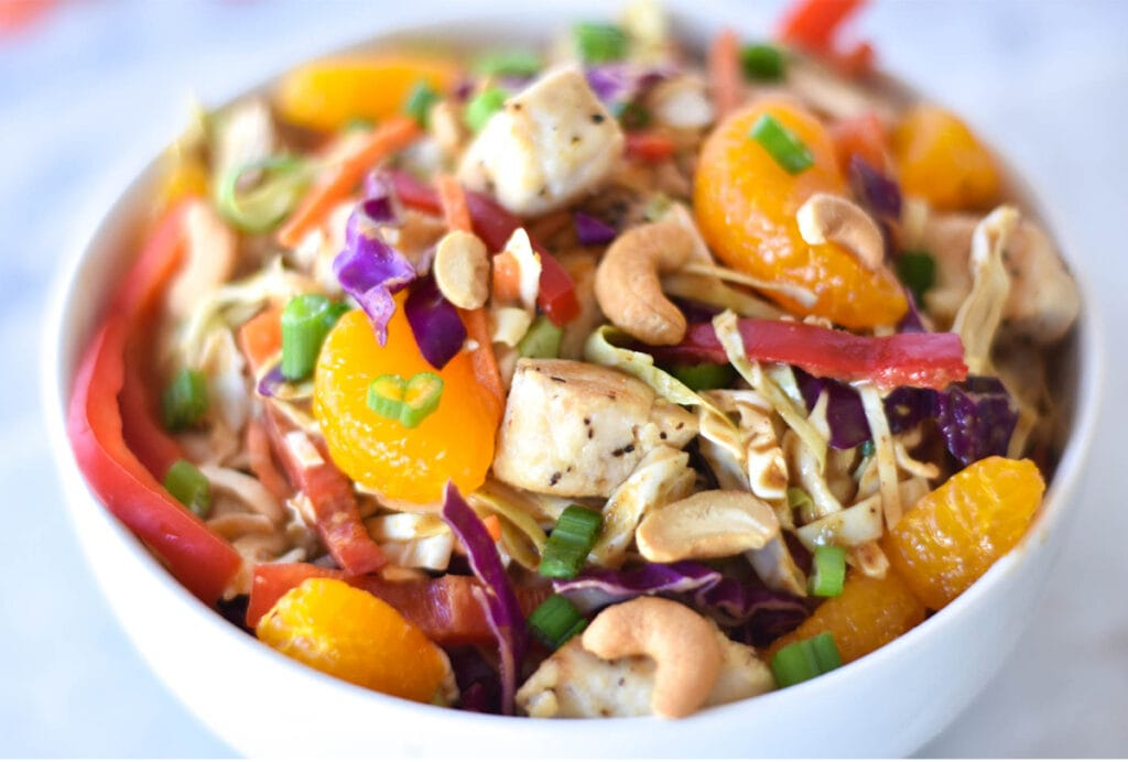 Bowl of Whole30 Asian Chicken Salad with brightly colored mandarin oranges, bell peppers, green onions, cabbage and cashews.