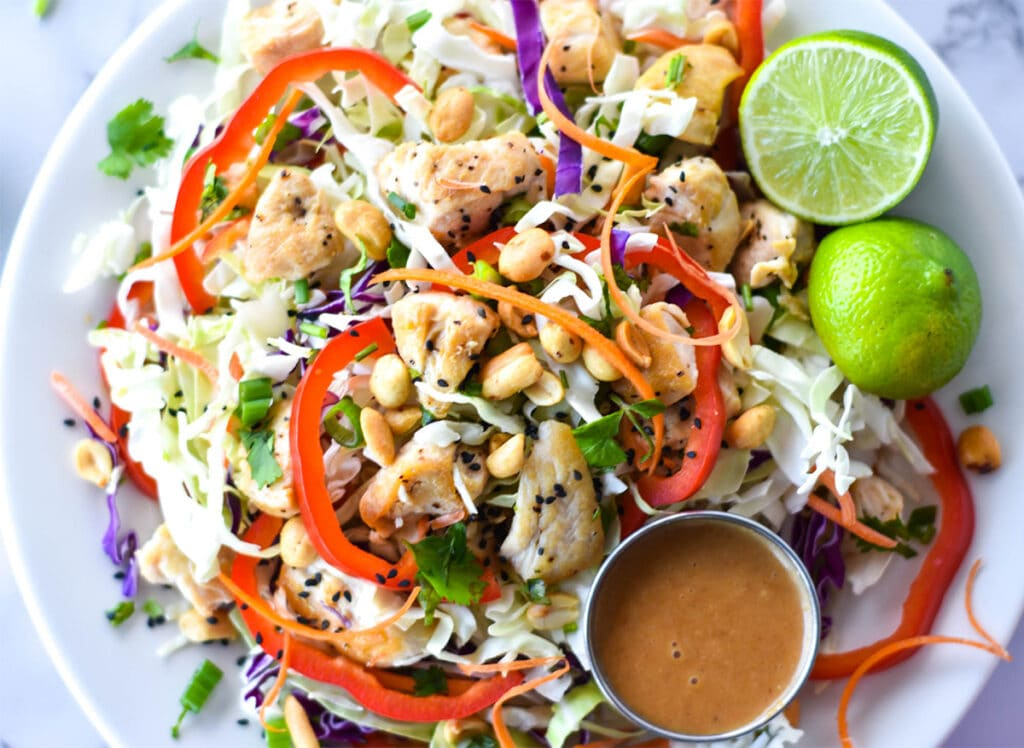 Large spicy Thai chicken salad with red bell pepper, green and purple cabbage, chicken, peanuts and carrots.
