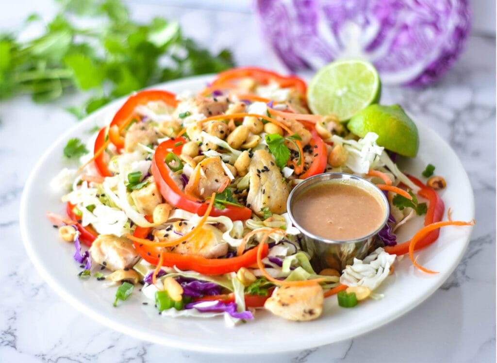 Large Thai chicken salad with red bell pepper, green and purple cabbage, chicken, peanuts and carrots next to a lime and peanut dressing.