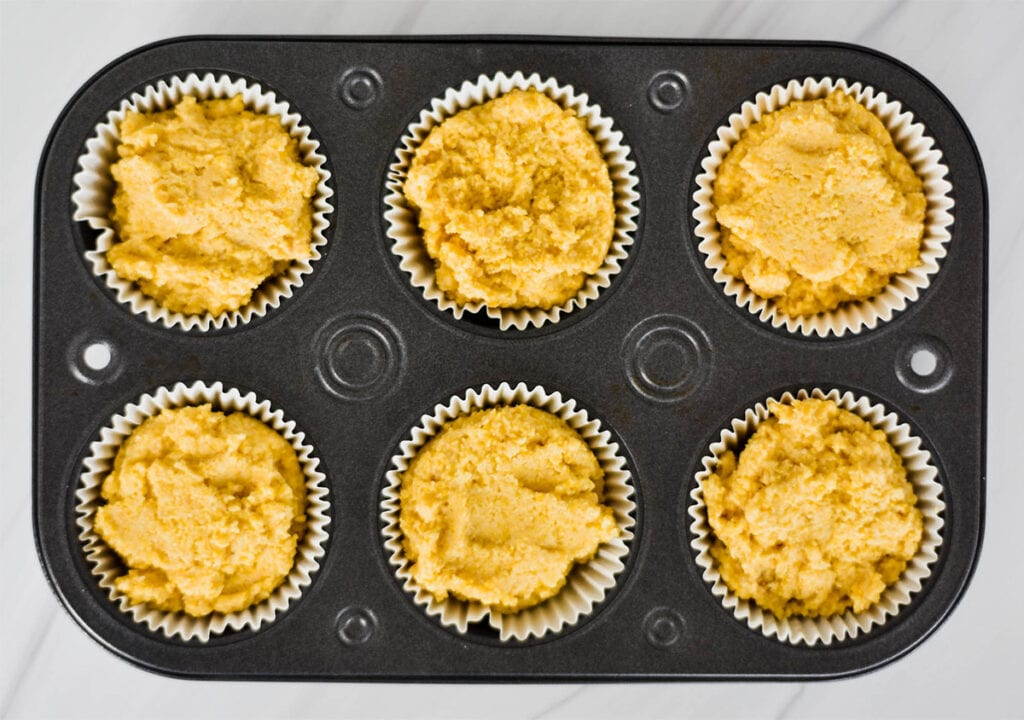 tray of unbaked cornbread muffins demonstrating that the muffin liners are filled comepletly.