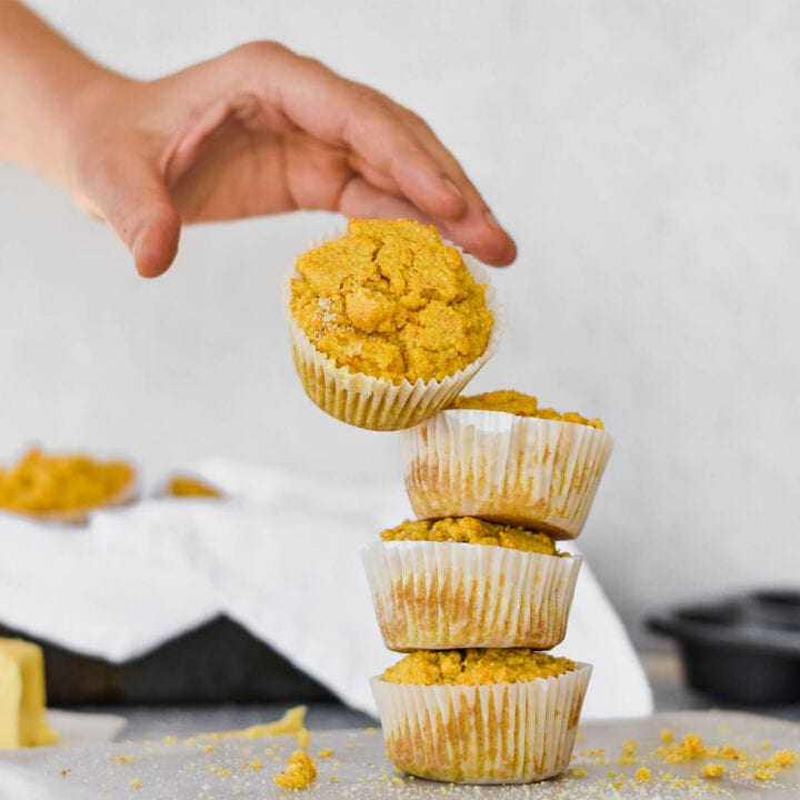 Hand tossing cornbread muffin on to stack.