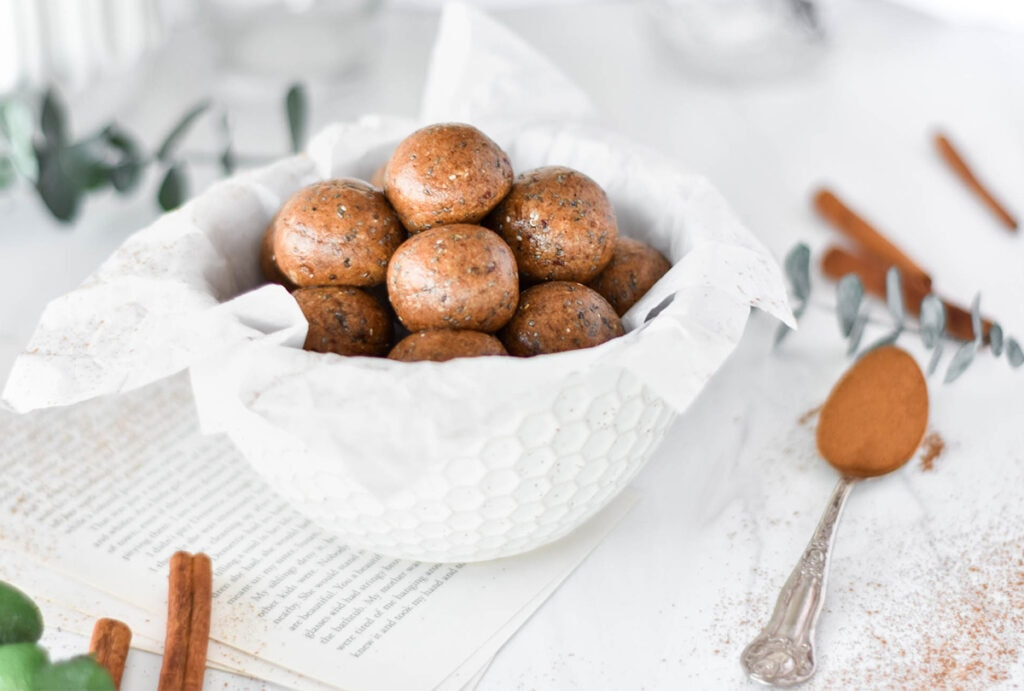 Bowl filled with brown protein balls covered with chia seeds next to cinnamon sticks and chai spices.