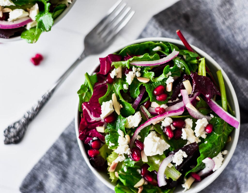 Brightly colored bowls of winter salad with feta, slivered almond, pomegranate seeds and mixed greens.