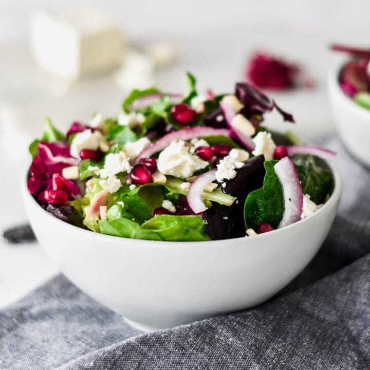 Brightly colored bowls of salad with feta, slivered almond, pomegranate seeds and mixed greens.
