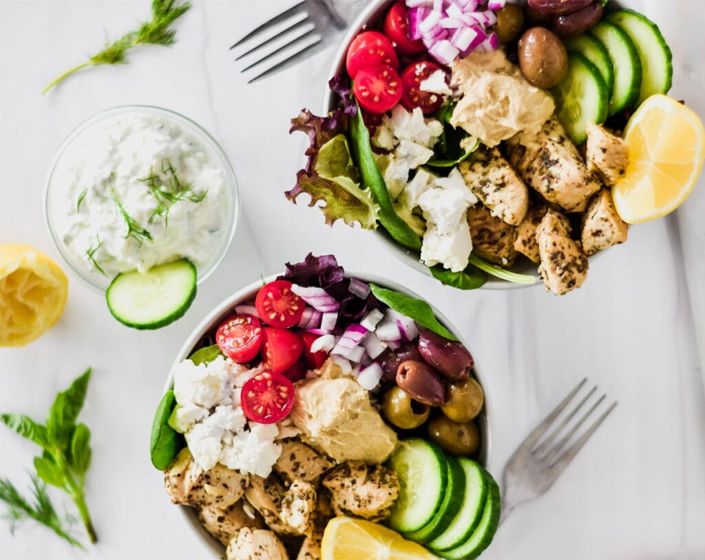 Low Carb Greek Chicken Bowls with cucumber, red onion, cherry tomatoes, Greek chicken hummus, feta and tzatziki.
