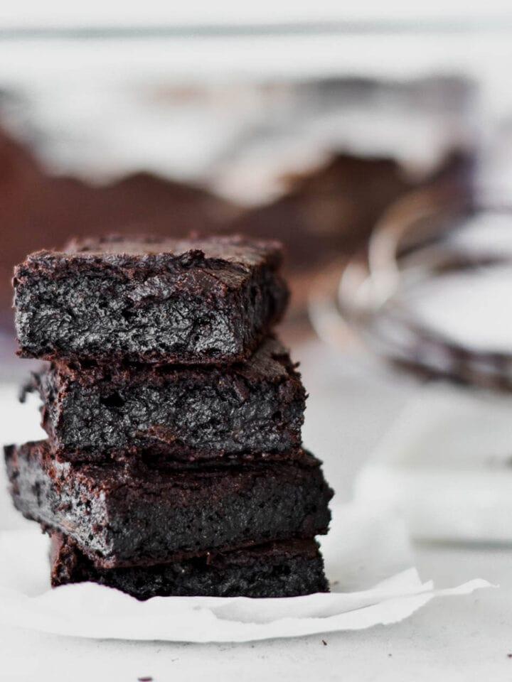 Stack of four dark chocolate paleo brownies.