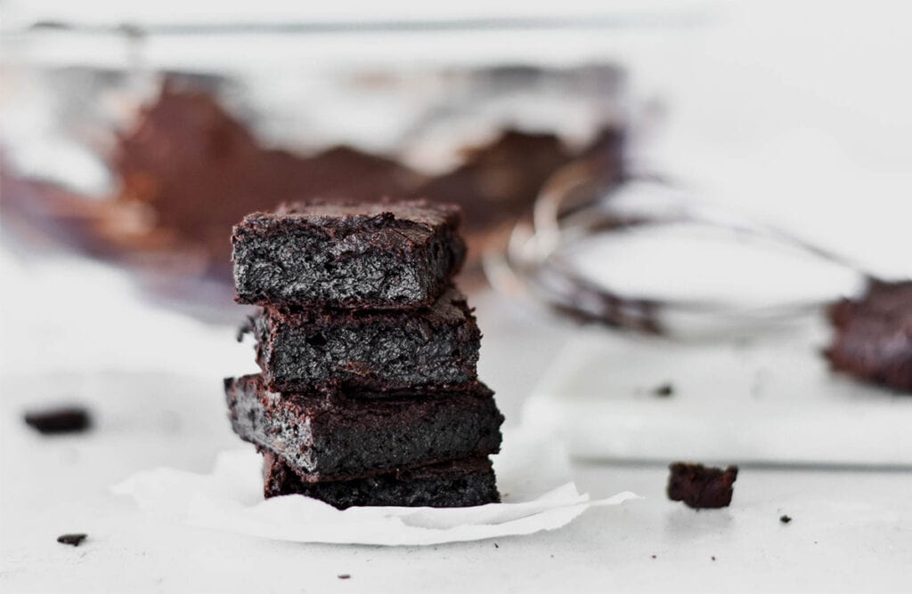 Stack of four dark chocolate paleo brownies.