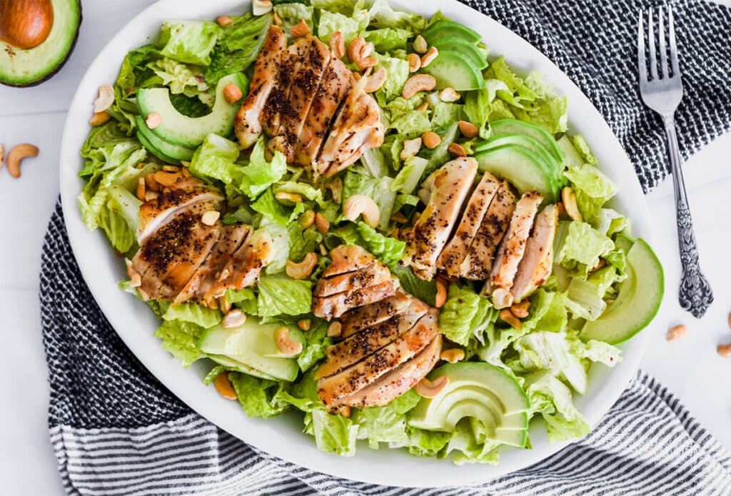 Brightly colored plate of green romatine lettuce, avocado and chicken.