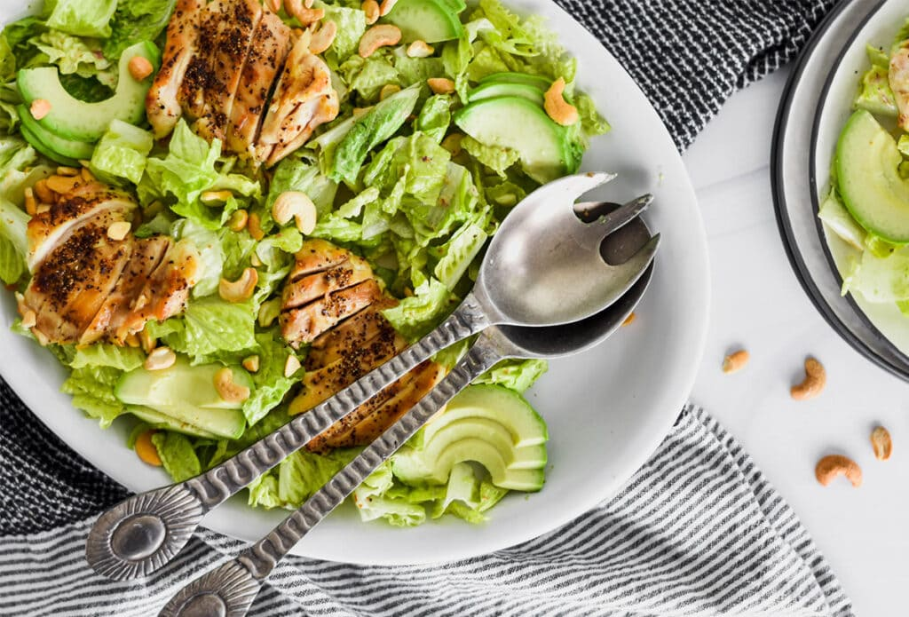 Brightly colored Whole30 Caesar Salad with green romatine lettuce, avocado and chicken.