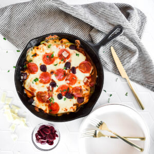 Cast iron skillet loaded with chicken breast and pizza toppings, covered in melted cheese.