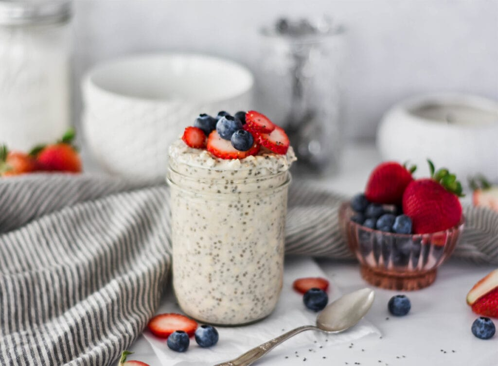 Mason jar overfilled with overnight oats topped with strawberries, blue berries and chia seeds.
