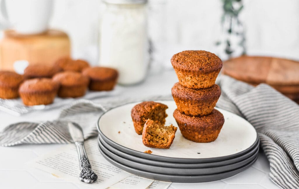 Stack of three paleo espresso banana muffins on a plate with one broken open.