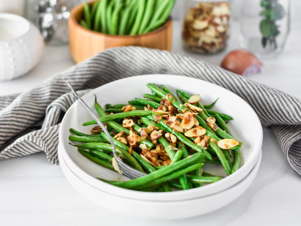 White plate filled with bright green green beans with almonds and shallot.
