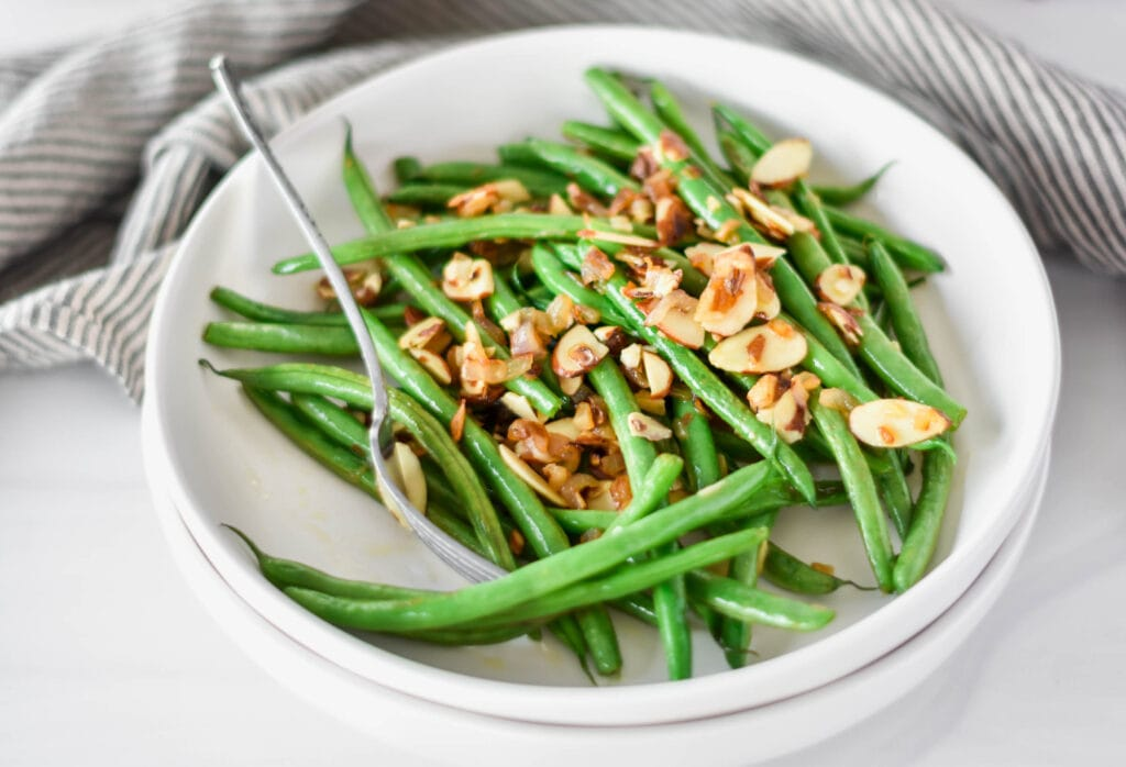 White plate filled with bright green whole30 green beans with almonds and shallot.