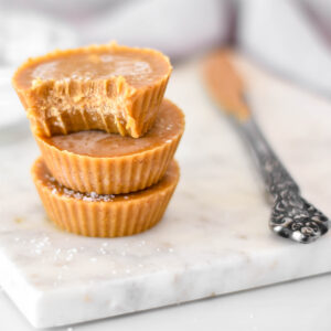 Stack of 3 dairy-free peanut butter fudge cups one with a bite out of it.