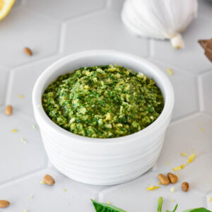 White dish filled with bright green lemon basil pesto.
