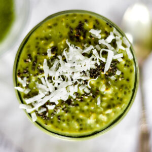 Top down view of bright green mactha overnight oats topped with coconut and chia seeds.