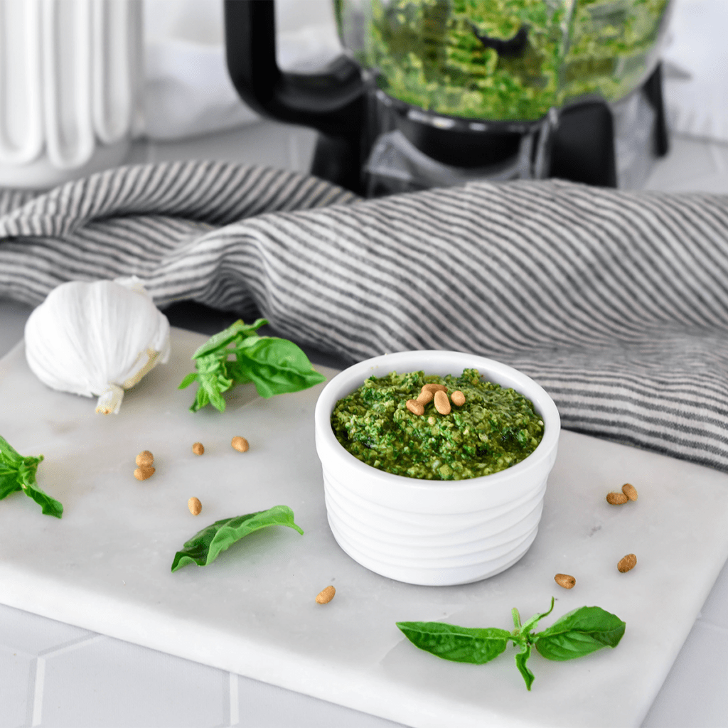 Dish filled with bright green pesto next to basil and garlic, topped with pine nuts.