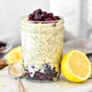 Mason jar filled with lemon overnight oats with blueberries layered in.
