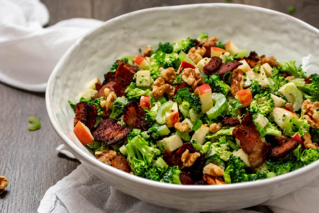 Bowl full of chopped broccoli salad with celery, apple, walnuts and bacon.