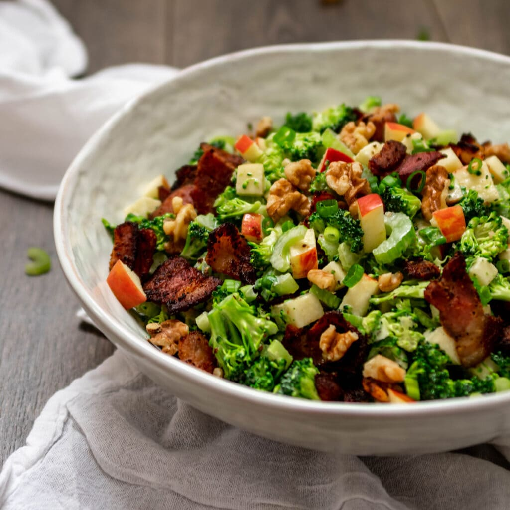 Bowl full of Paleo Broccoli Salad with bacon, apple and walnuts.