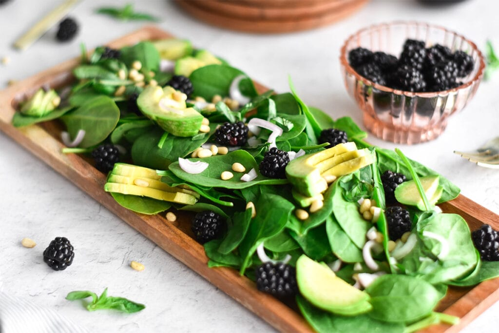 Brightly colored paleo blackberry avocado salad with shallot and blackberry vinaigrette.