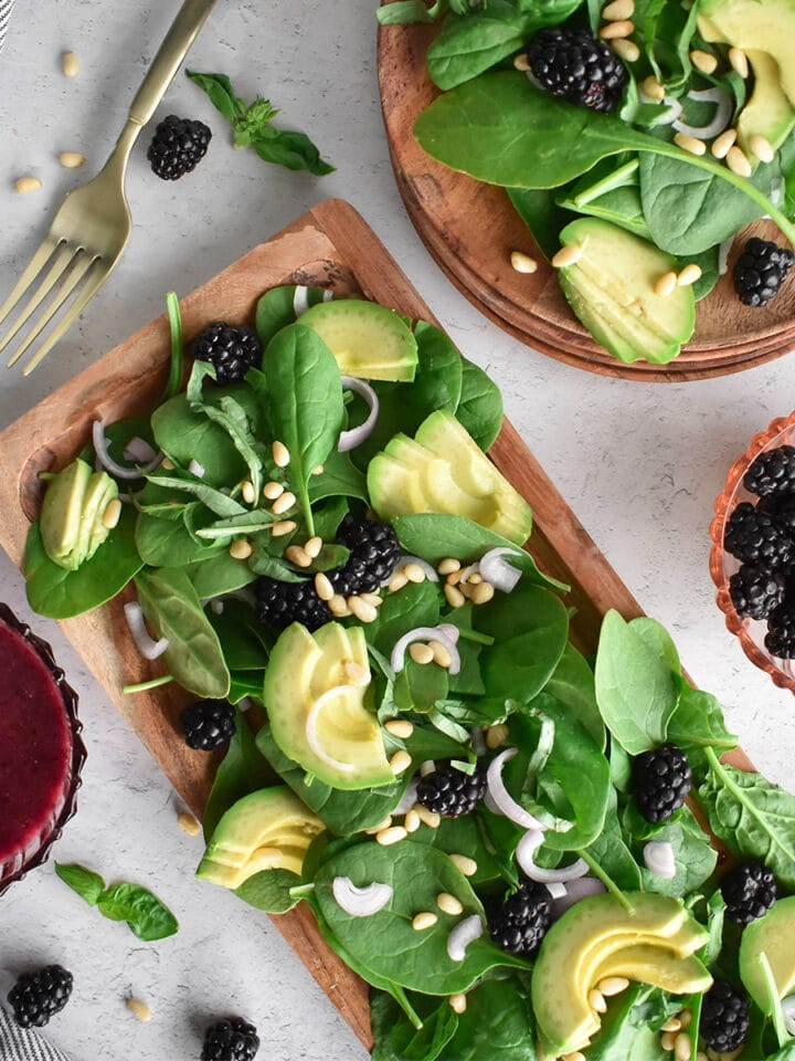 Wooden platter filled with greens, blackberries, avocado, pine nuts and shallot.