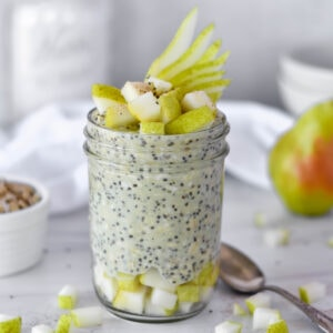 Pear overnight oats in mason jar next to a pear and a bowl of oats.
