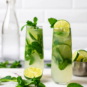 Two keto mojitos garnished with lime and mint.