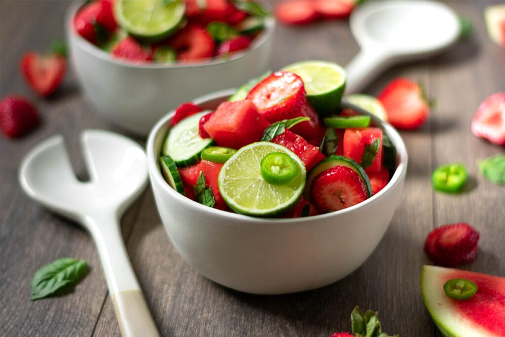 Two bowls full of vegan, paleo watermelon salad with lime, jalapeño, cucumber and strawberry.