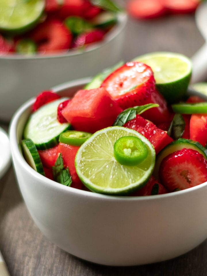 Bowl full of paleo vegan watermelon salad with lime, jalapeño, cucumber and strawberry.