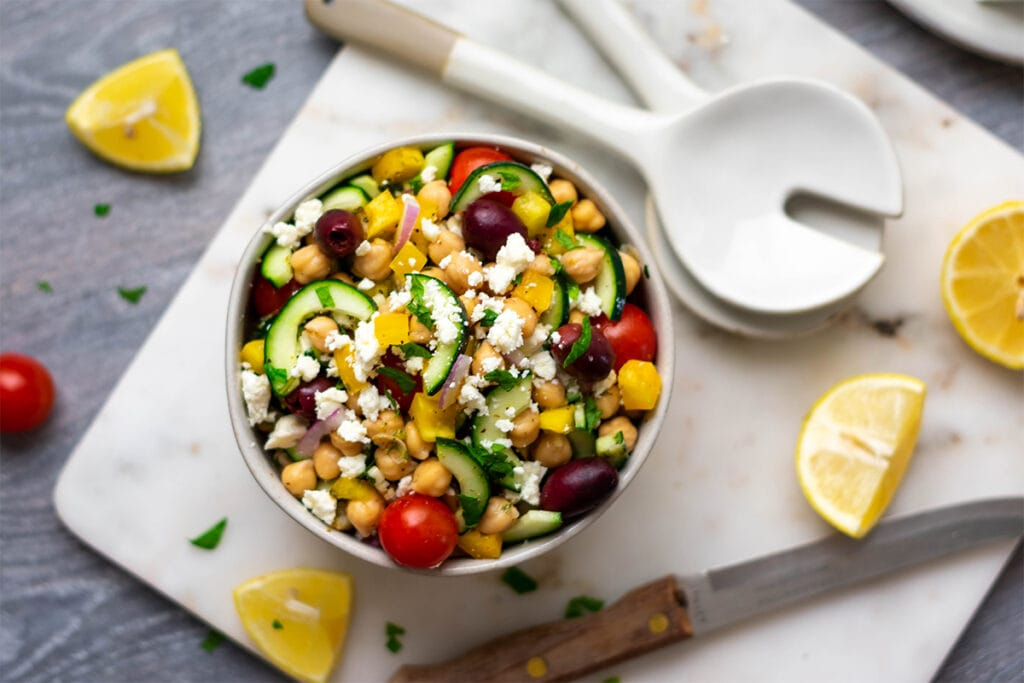 Bowl of Greek chickpea salad with cherry tomatoes, cucumber, olives, red onion, bell pepper and feta.