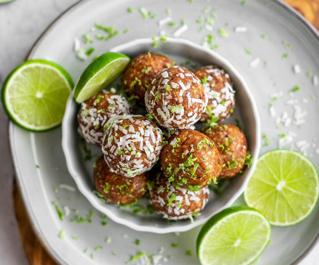 Dish filled with key lime pie energy balls covered in coconut and lime zest.