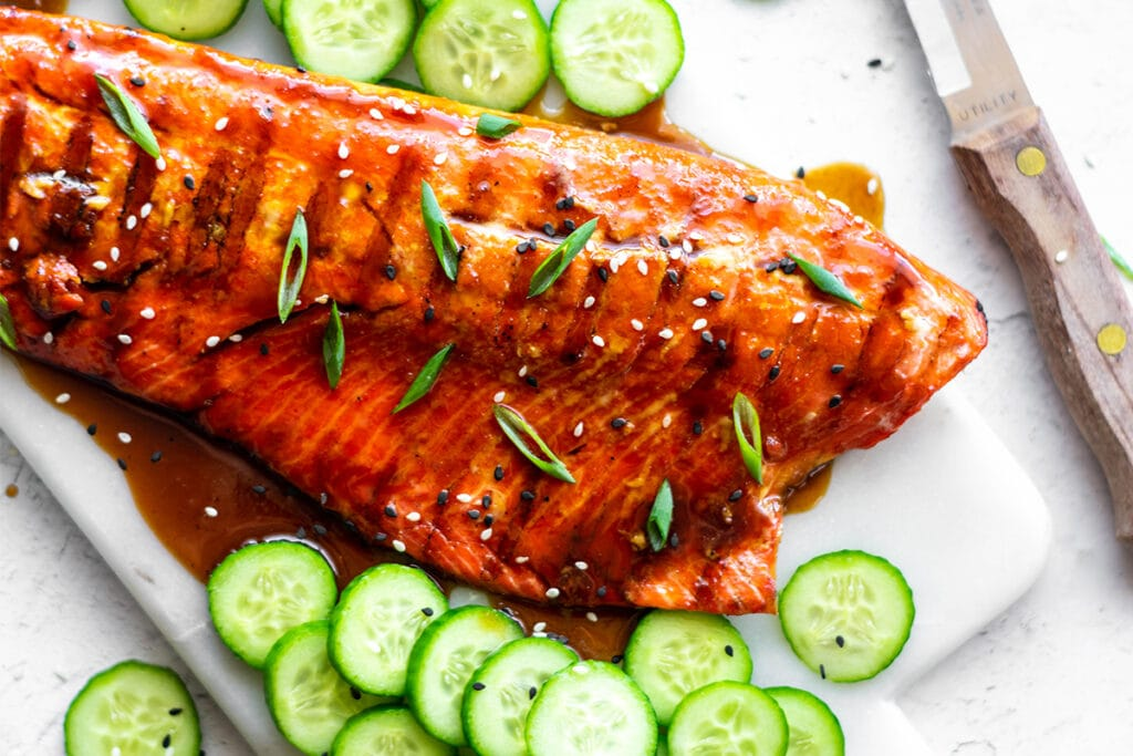 Salmon filets covered with paleo teriyaki sauce, sesame seeds and green onions.