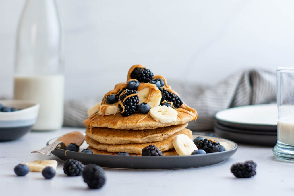 Stack of vegan oat pancakes with blackberries, peanut butter and banana slices on top.