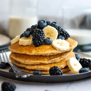 Stack of vegan oatmeal pancakes with blackberries, blueberries and banana on top.