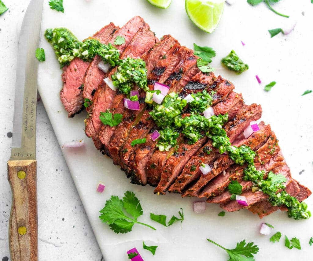 Sliced paleo carne asada with a bright green sauce with cilantro and red onion.