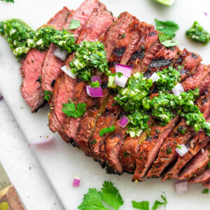 Sliced carne asada with a bright green sauce with cilantro and red onion.