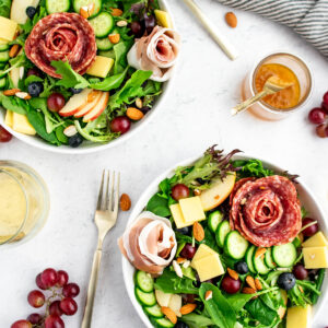 Charcuterie salad with nuts, salami, cheese, grapes, blueberries, olives and cucumbers.