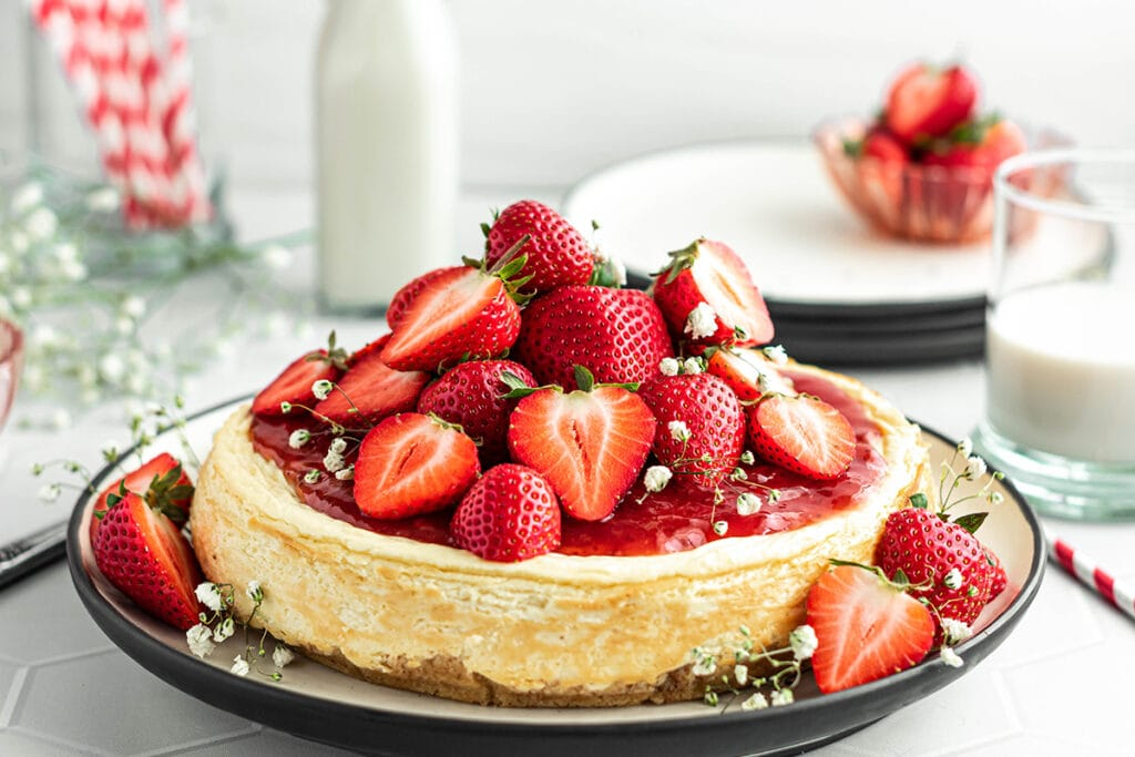 Keto cheese cake topped with strawberries and strawberry sauce.