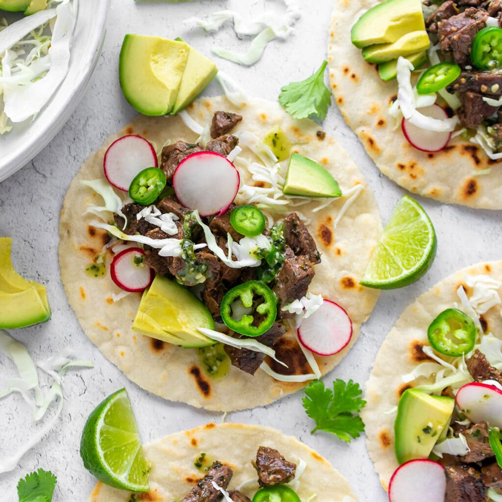Paleo carne asada tacos with beef, avocado, radish, cabbage and jalapeno.