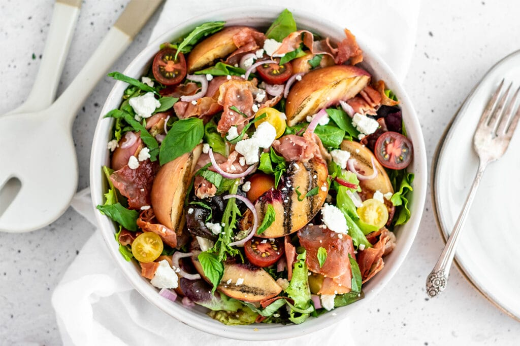 Brightly colored grilled peach and prosciutto salad with peaches, crispy prosciutto, creamy goat cheese, shallot, basil and greens.